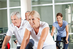 Senior people on spinning bikes Stock Photos