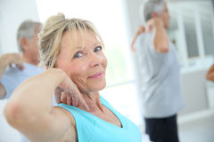Senior people stretching in fitness room Stock Photo