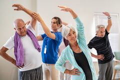 Free Senior People Stretching With Trainer At Retirement Community Royalty Free Stock Images - 217898449