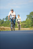 Senior people taking bike trip with bicycle helmets. Two senior people taking bike trip with bicycle helmets in summer royalty free stock image