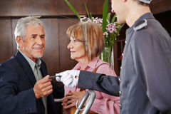 Senior people taking key card from concierge Stock Photo