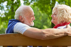 Senior people talking and flirting on a park bench Royalty Free Stock Images