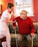 Senior people with walking crutches. Having assistance of a loving nurse stock images