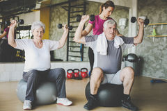 Senior people workout in rehabilitation center. Senior people with personal fitness trainer Royalty Free Stock Images