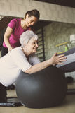 Senior people workout in rehabilitation center. Personal trainer helping senior people on Pilates ball Royalty Free Stock Photos