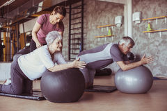 Senior people workout in rehabilitation center. Personal trainer helping senior people on Pilates ball Stock Image