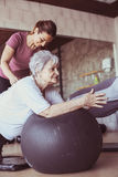 Senior people workout in rehabilitation center. Personal trainer helping senior people on Pilates ball Stock Images