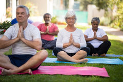Senior peoplemeditating in prayer position Stock Photos