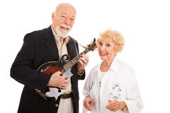 Senior Performers. Musical senior couple.  He plays mandolin and she sings along.  Isolated on white Royalty Free Stock Photos