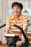 Senior person exercises - spinning. Mature (senior) woman exercises on spinning bicycle at home (room interior in background Royalty Free Stock Photos
