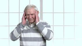 Senior person with headache, blurred background. Elderly man holding his hands on his temples as he suffering from a headache or migraine stock video