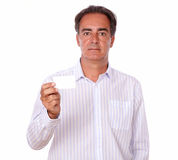 Senior person holding a blank business card. Portrait of a senior person on white shirt holding a blank business card while standing on isolated background Royalty Free Stock Images