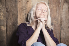 Senior person pray with a wood background Stock Image