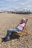 Senior person sitting in a deckchair on a beach. Elderly man wearing a knotted hankerchief on his head relaxing on the beach. Southsea, England UK Royalty Free Stock Photo