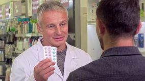 Senior pharmacist giving blisters with pills to a male customer stock video