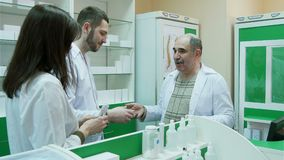 Senior pharmacist giving salary in dollar to his young colleagues at pharmacy stock footage
