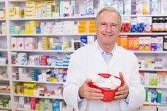 Senior pharmacist holding bowl of medicines Royalty Free Stock Images