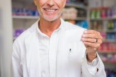 Senior pharmacist holding calling card Royalty Free Stock Photos