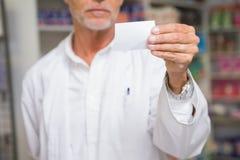 Senior pharmacist holding calling card Royalty Free Stock Image