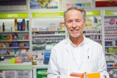 Senior pharmacist holding many medicines Royalty Free Stock Image