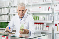 Senior Pharmacist Holding Product While Writing On Clipboard. Portrait of senior pharmacist holding product while writing on clipboard in pharmacy Royalty Free Stock Images