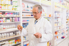 Senior pharmacist looking at medicine and prescription Stock Photos
