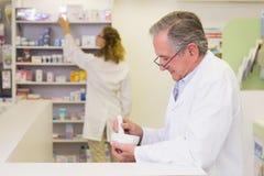 Senior pharmacist mixing a medicine Stock Photos