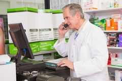 Senior pharmacist phoning while using computer Royalty Free Stock Photography