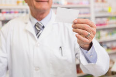 Senior pharmacist reading calling card Royalty Free Stock Image
