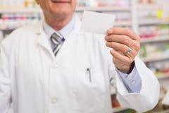 Senior pharmacist reading calling card Royalty Free Stock Image