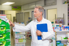 Senior pharmacist reading medicine and holding clipboard Royalty Free Stock Photo