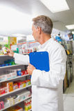 Senior pharmacist reading medicine and holding clipboard Royalty Free Stock Images