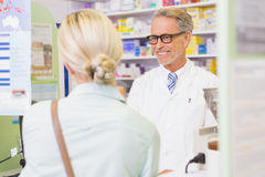 Senior pharmacist speaking with customer Royalty Free Stock Image