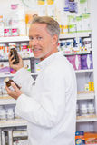 Senior pharmacist taking jar from shelf Royalty Free Stock Images
