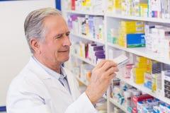 Senior pharmacist taking medicine from shelf. At the hospital pharmacy Stock Photos