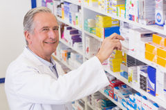 Senior pharmacist taking medicine from shelf Royalty Free Stock Photography