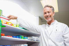 Senior pharmacist taking medicine from shelf. In the pharmacy Royalty Free Stock Photos