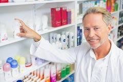 Senior pharmacist taking medicine from shelf Stock Photos
