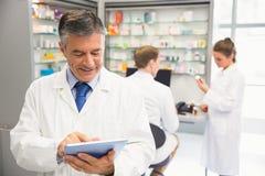 Senior pharmacist using tablet pc Stock Images