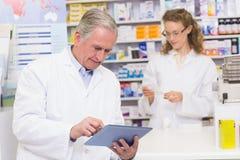 Senior pharmacist using tablet pc Royalty Free Stock Image
