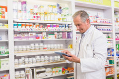 Senior pharmacist using tablet pc. In the pharamcy Stock Image