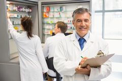 Senior pharmacist writing on clipboard Royalty Free Stock Images