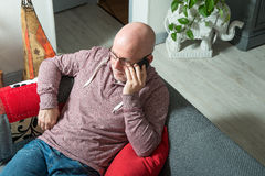 A senior with a phone sitting on the sofa. In his house Royalty Free Stock Photo