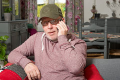A senior with a phone sitting on the sofa. In his house Stock Photography