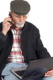 Senior phoning with laptop computer Stock Photography