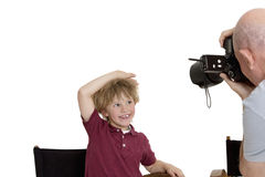 Senior photographer clicking school kid sitting on chair over white background Royalty Free Stock Photo