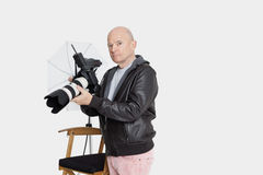 Senior photographer holding camera standing in studio royalty free stock images