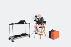 Senior photographer looking at camera while sitting on director's chair in studio Stock Images