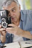 Senior photographer with retro camera. Senior photographer holding vintage camera royalty free stock photography
