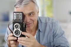 Senior photographer with retro camera. Senior photographer holding vintage camera royalty free stock image
